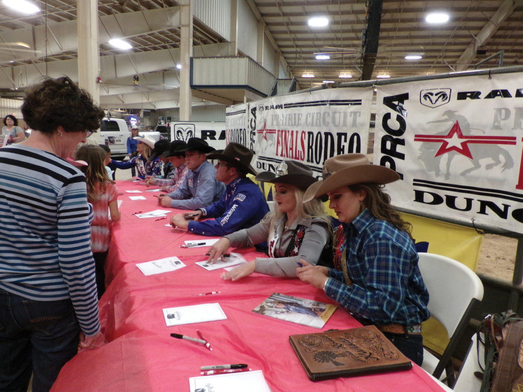 Rodeo Queens and event winners sign autographs for fans.